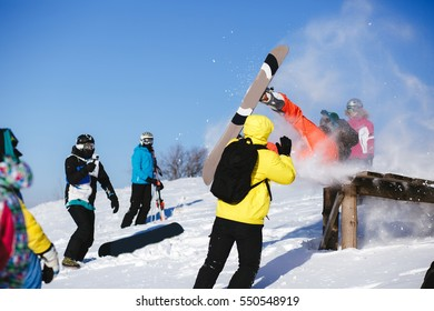 Snowboarder jump from wooden springboard in the mountains