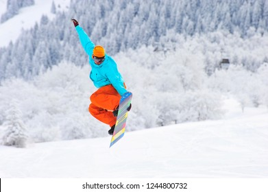 Snowboarder is jumping in the air at mountains