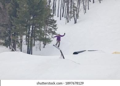 A snowboarder jumping high through the air at the Wisp Ski Resort in Deep Creek Lake Maryland