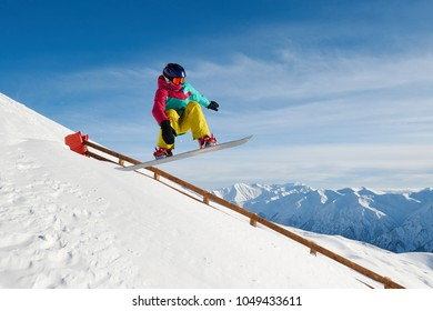 snowboarder jumping near a fence in the mountains