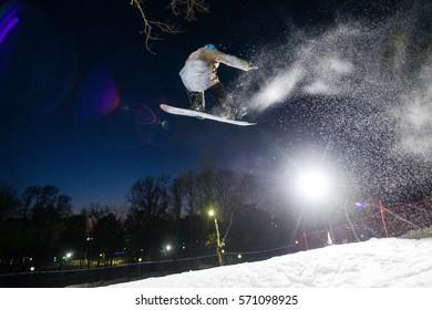 Snowboarder jumping at night snow spray 1