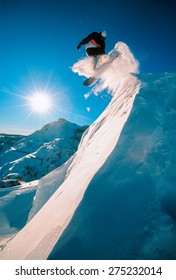 Snowboarder jumping off a cliff off piste, backlit by the sun on a sunny day in Donner Pass, California, USA.