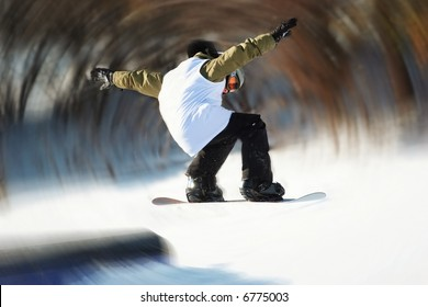 Snowboarder jumping off a rail