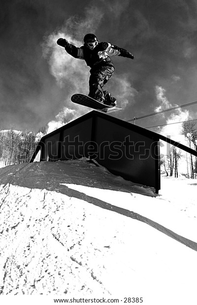 Snowboarder jumping on to a rail.