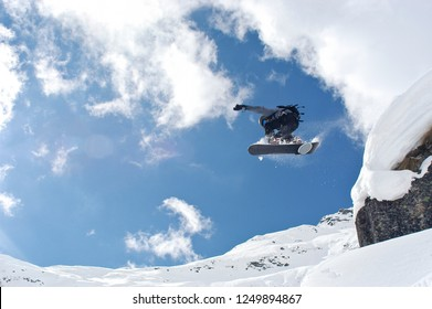 Snowboarder jumping over rocks