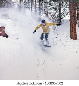 Snowboarder jumping over the snow-covered stone on the background forest. Low angle view.