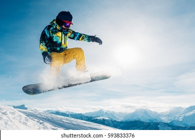 snowboarder is jumping with snowboard from snow hill in the sun beam