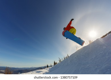 Snowboarder jumping through air with deep sunset sky in background
