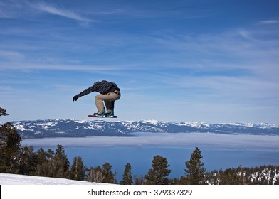 A snowboarder jumps over mountains and Lake Tahoe, California.