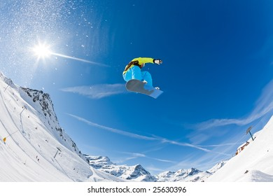 Snowboarder launching off a jump; Gressoney , Aosta, Italy.