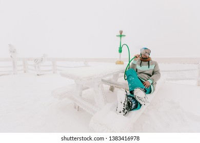 Snowboarder man relaxing and smoke a hookah or shisha, winter frozen day, snow and frost on the branch and table outdoor