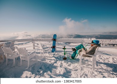 Snowboarder man relaxing and smoke a hookah or shisha, enjoying mountain view, winter frozen day, snow and frost on the branch and table outdoor