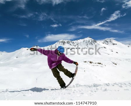 8162540b4c1e Snowboarder in mountains taking for the edge snowboard against the blue sky  and clouds