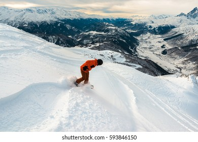 snowboarder on the red suit is riding with snowboard from powder snow hill or mountain
