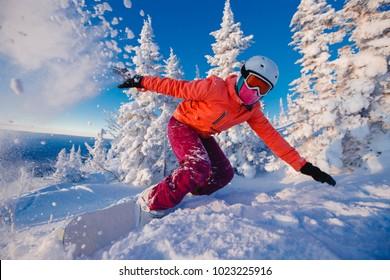 Snowboarder on snowboard rides through snow, explosion. Freeride snowboarding in Sheregesh Ski Resort