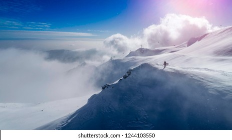 Snowboarder on the summit . Extreme sport. Snowboarder on mountain top. Freeride scene, Aerial view on top of a mountain. Ski resort. Carpathians mountains landscape. Winter sports. Freeride slope