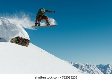 the snowboarder in the outfit drops off the ledge of the stone onto the fresh snow creating a spray