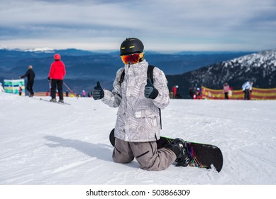 Snowboarder posing at the mountain top.