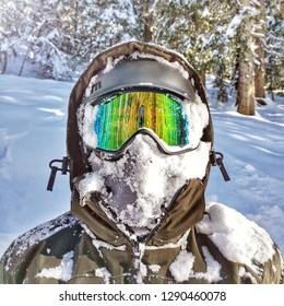 Snowboarder in powder - Snowboarder portrait - Snow on face - Snowboard goggles