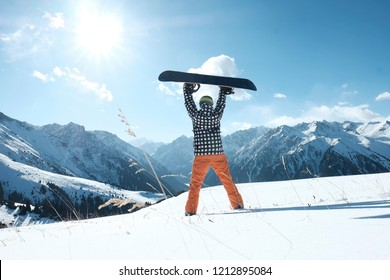 snowboarder raises a snowboard over his head, stands on the snow clear day,