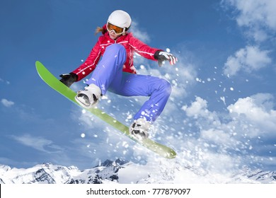 Snowboarder in red jacket and lilac trousers jumps on her green snowboard through the air in front of a mountain panorama and winter landscape