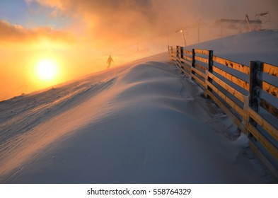 Snowboarder ride on the top of the snowy hill during beautiful winter windy sunset. Ski lift in winter resort in background. Sport active wallpaper with space for your montage.