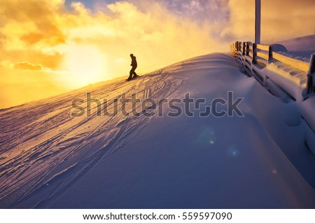Snowboarder ride on the top of snowy hill in ski resort during calm winter sunset. Scenery of athlete - wallpaper with space for your montage