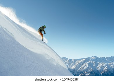 snowboarder rides on a steep mountainside on a beautiful landscape