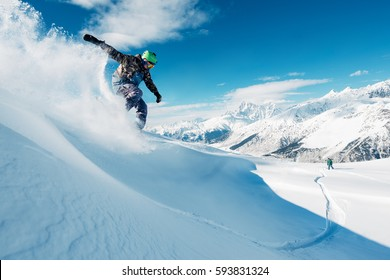 snowboarder is riding with snowboard from powder snow hill or mountain very fast