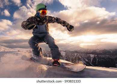 snowboarder is riding with snowboard from powder snow hill or mountain on the beautiful sunset