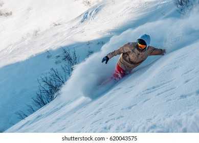 snowboarder is riding with snowboard from powder snow hill