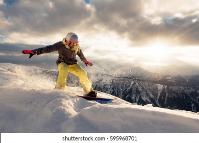 snowboarder is riding with snowboard from snow hill in the sun beam on the sunset