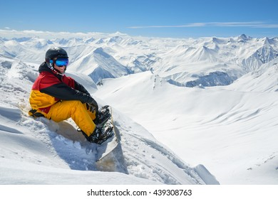 snowboarder sits high in the mountains on the edge of the slope and looks into the distance.