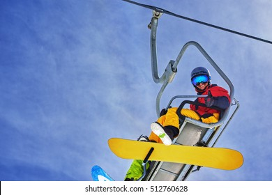 Snowboarder sitting on the chairlift and smiling, close-up view from below.