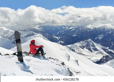 Snowboarder sitting on the edge of the mountain and enjoy the winter landscape.