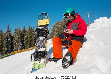Snowboarder sitting in the snow at ski resort,using his smart phone while resting in the mountains technology communication carrier mobility recreation sport lifestyle