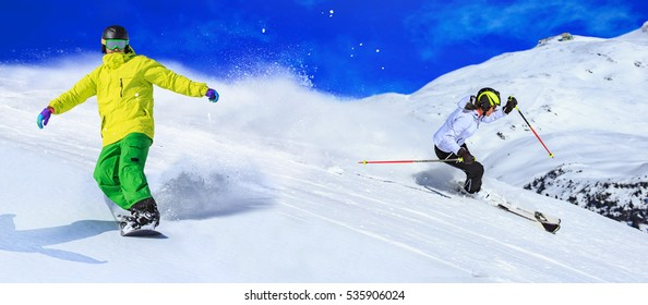 A snowboarder an a ski driver on the piste in Alps in Austria