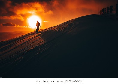 Snowboarder in ski resort. Winter sport photo. Orange sunset light in background. Edit space. Christmas and New Year time, snowy photo, edit space