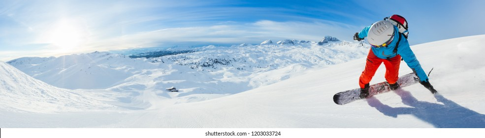 Snowboarder skiing downhill, panoramic format. Winter sports and leasure activities