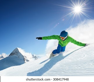 Snowboarder skiing in high mountains at beautiful sunny day. Clear weather and sky, prepared snow / piste.
