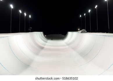 Snowboarder in a snow halfpipe at night lit up by lights