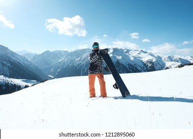 snowboarder with snowboard standing on the snow,