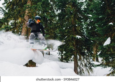 snowboarder with special equipment is riding fast, jumping, freeriding in the mountain forest