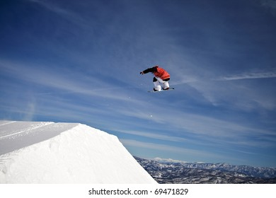 Snowboarder spins through the air at winter mountain resort