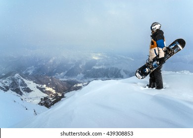 Snowboarder standing on a cliff in the snowy weather in the mountains.
