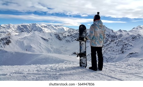 Snowboarder standing on a cliff in the snowy weather in the mountains