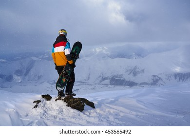 Snowboarder standing on a rock on the edge of a cliff and looking down.