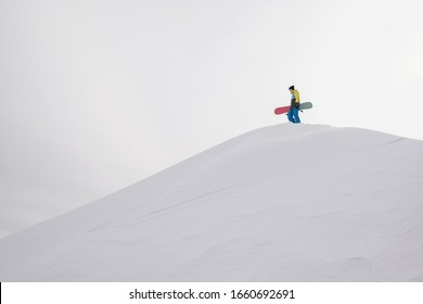 Snowboarder standing on a slope holding board. White snow background