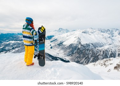 Snowboarder is standing with snowboard in the mountain