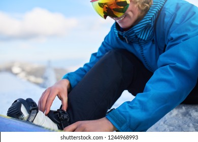 Snowboarder straps in his legs in snowboard boots in modern fast flow bindings with straps. Rider at ski resort prepares for freeride session and . Man wearing fashionable outfit. Feet close-up.